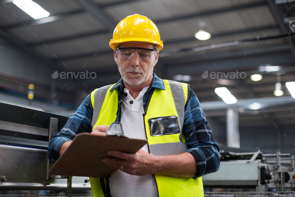 Male factory worker maintaining record on clipboard - Stock Photo - Images