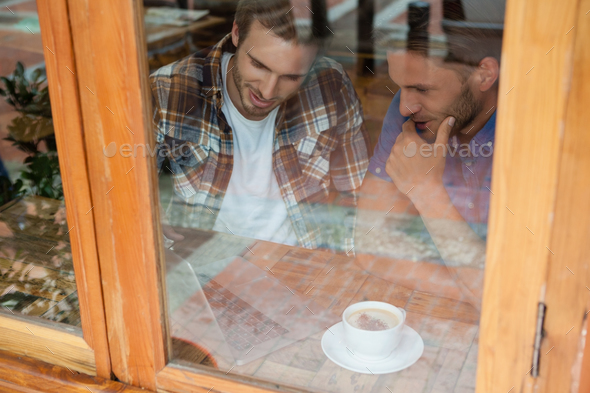 Friends sitting by window at cafe shop - Stock Photo - Images