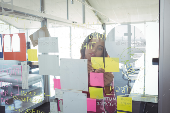 Businesswoman seen through adhesive notes on glass in creative office - Stock Photo - Images