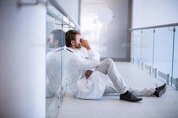 Tensed doctor sitting in corridor - Stock Photo - Images