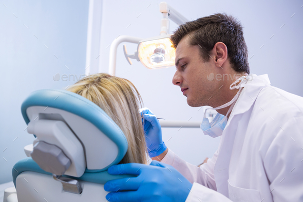 Side view of dentist polishing  woman teeth - Stock Photo - Images