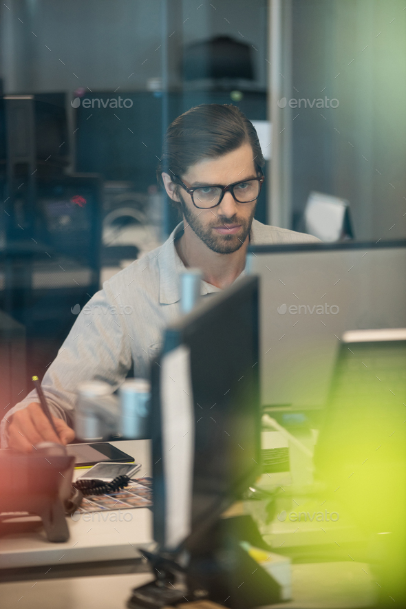 Concentrated businessman working on digitizer in office - Stock Photo - Images
