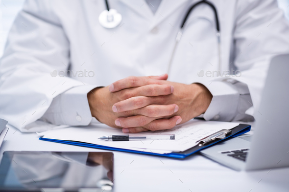 Mid section of doctor sitting at desk - Stock Photo - Images