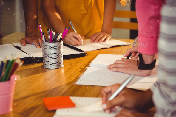 Mid section of business executives writing in book - Stock Photo - Images