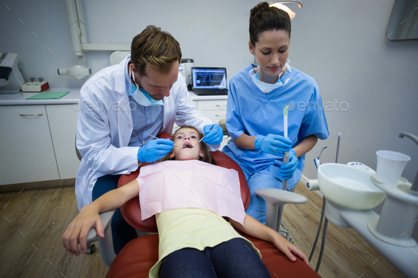Dentists examining a young patient with tools - Stock Photo - Images