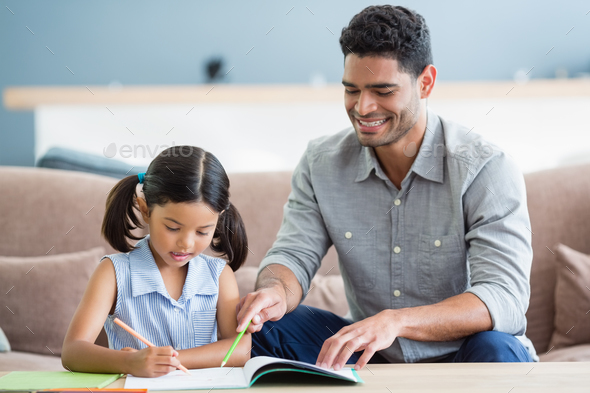 Father assisting her daughter in doing her homework - Stock Photo - Images