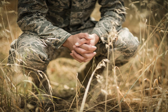 Military soldier crouching in grass - Stock Photo - Images