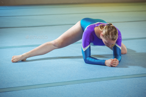 Female gymnast performing stretching exercise - Stock Photo - Images