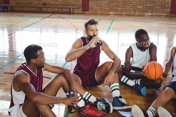 Basketball players interacting while relaxing - Stock Photo - Images