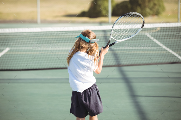 Rear view of girl playing tennis - Stock Photo - Images