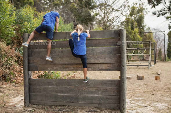 Fit man and woman climbing over wooden wall during obstacle course - Stock Photo - Images