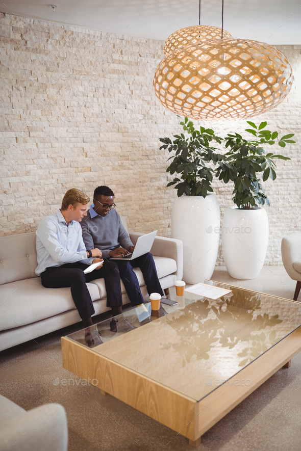 Attentive executives using digital tablet and laptop - Stock Photo - Images
