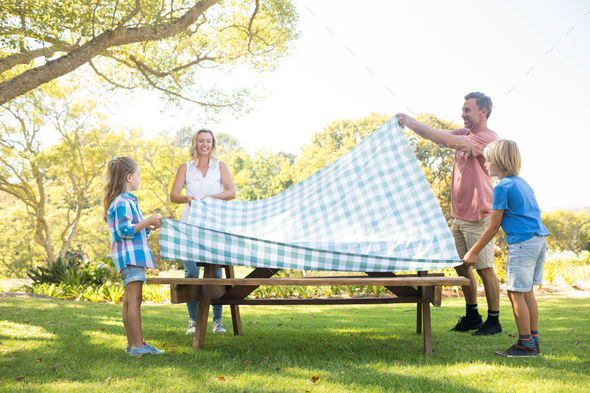 Family spreading the tablecloth on picnic table - Stock Photo - Images