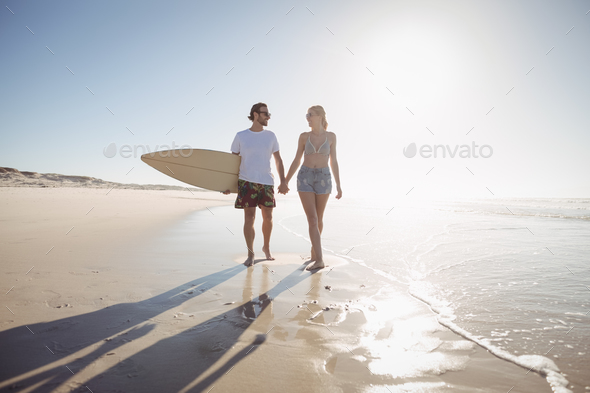 Young couple holding hands at beach during sunny day - Stock Photo - Images