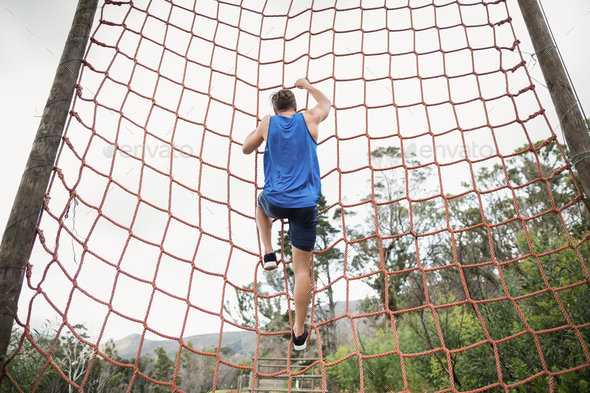 Man climbing a net during obstacle course - Stock Photo - Images