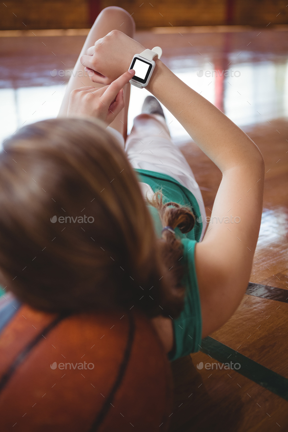 Female basketball player using smart watch - Stock Photo - Images