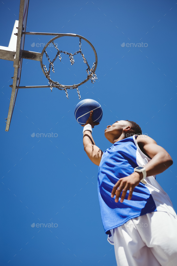 Low angle view of teenager playing basketball - Stock Photo - Images