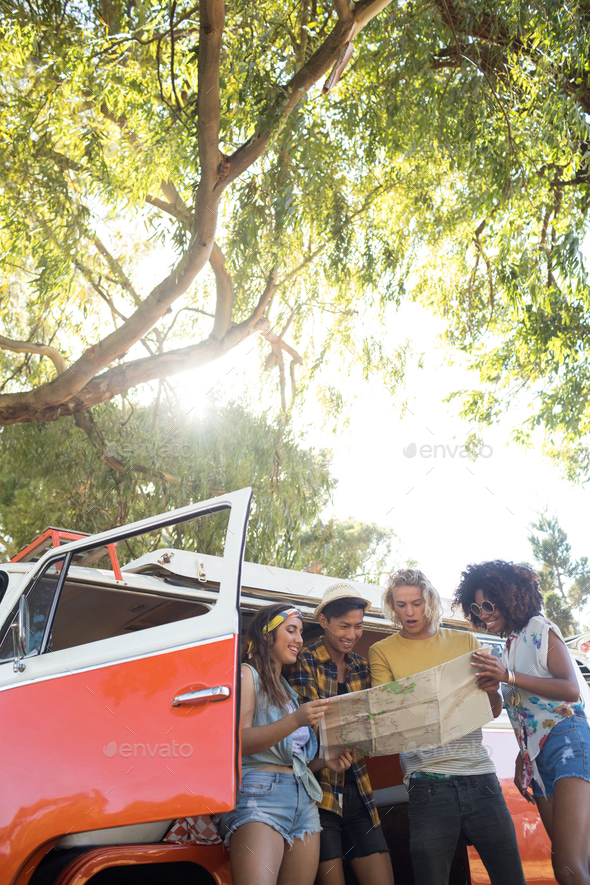 Low angle view of friends reading map at campsite - Stock Photo - Images
