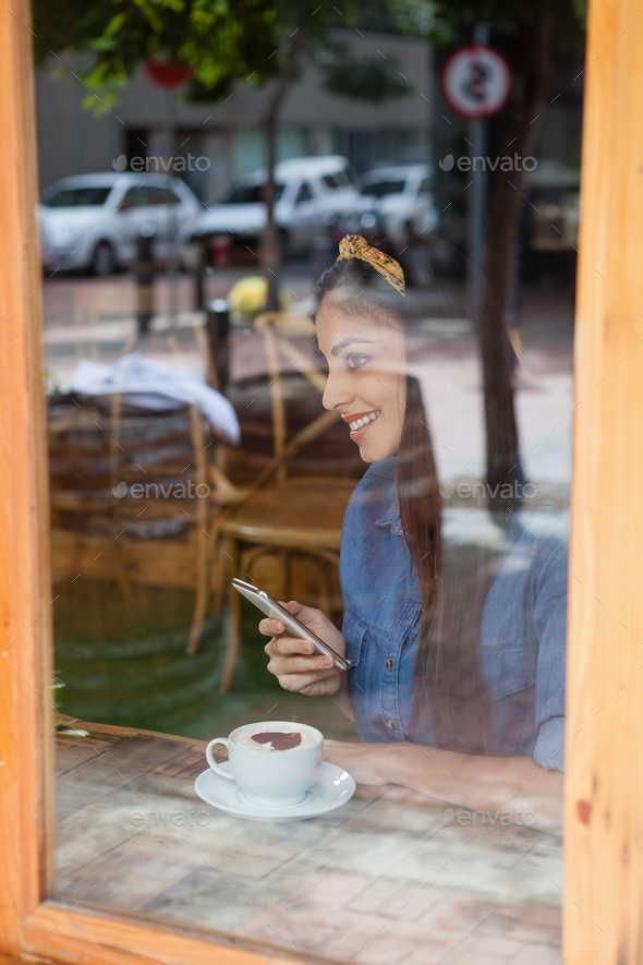 Smiling woman holding mobile phone while sitting at cafe - Stock Photo - Images