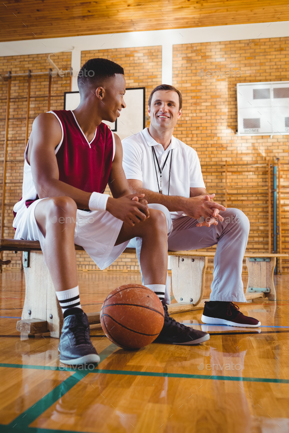 Smiling coach and player talking in court - Stock Photo - Images
