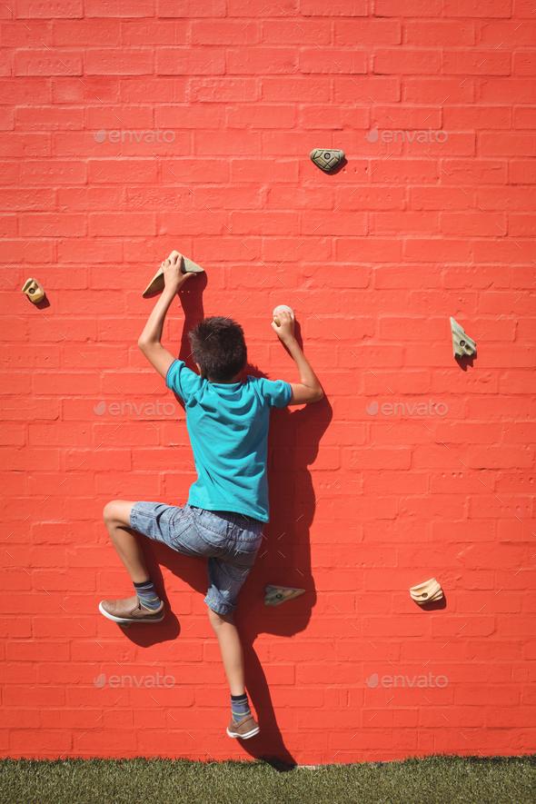Boy climbing orange wall - Stock Photo - Images