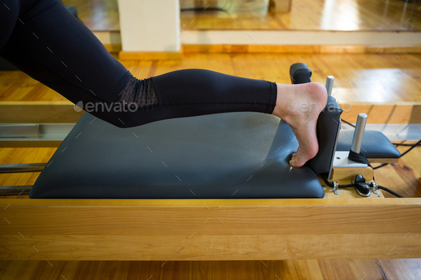 Woman practicing stretching exercise on reformer - Stock Photo - Images