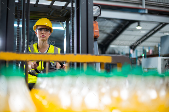 Female factory worker driving forklift in factory - Stock Photo - Images