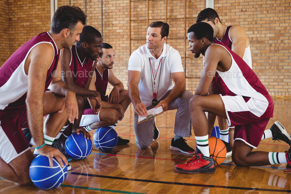 Coach explaining game plan to basketball players - Stock Photo - Images