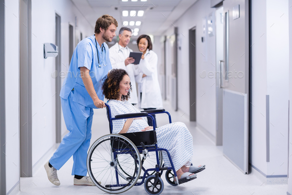 Doctor pushing a pregnant woman on wheelchair - Stock Photo - Images