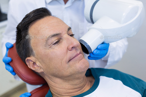 Mid section of dentist examining a male patient with dental tool - Stock Photo - Images