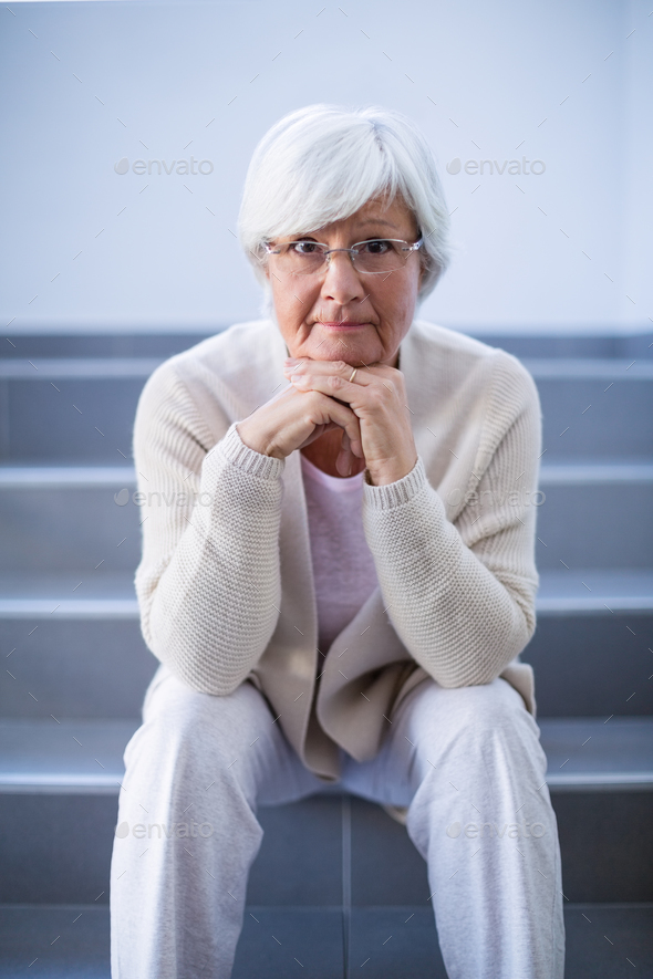Portrait of senior woman sitting on stairs - Stock Photo - Images