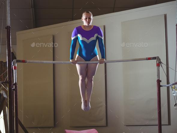 Female gymnast practicing gymnastics on the horizontal bar - Stock Photo - Images
