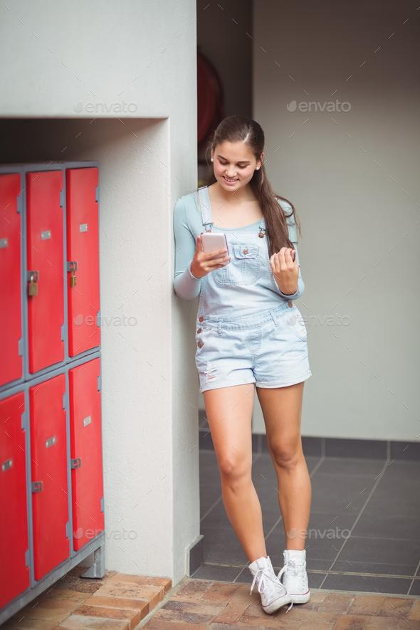 Schoolgirl using mobile phone in locker room - Stock Photo - Images