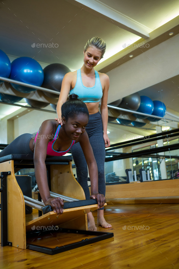Trainer assisting woman with wunda chair in fitness studio - Stock Photo - Images