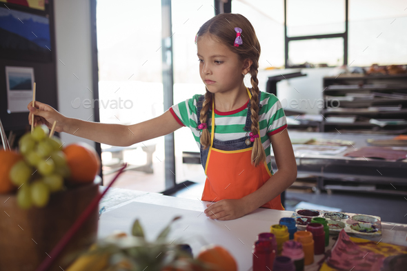 Girl painting at desk in classroom - Stock Photo - Images