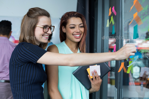 Smiling business executive sticking sticky note on glass - Stock Photo - Images