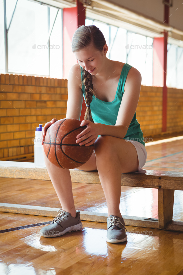 Smiling woman holding basketball while sitting on bench - Stock Photo - Images
