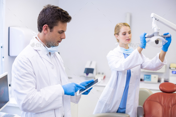Dentist using digital tablet while his colleague adjusting dental light in background - Stock Photo - Images