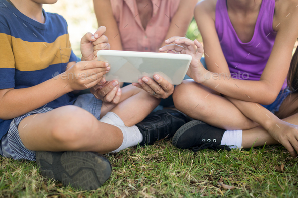 Grandmother and grand kids using digital tablet in the park - Stock Photo - Images