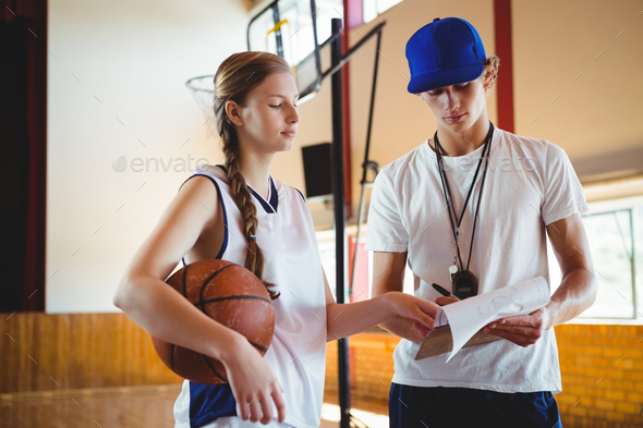Female basketball player discussing with male coach - Stock Photo - Images