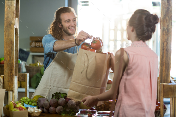 Vendor handing a bag of vegetables to woman at grocery store - Stock Photo - Images