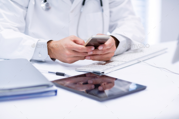 Mid section of doctor using mobile phone - Stock Photo - Images