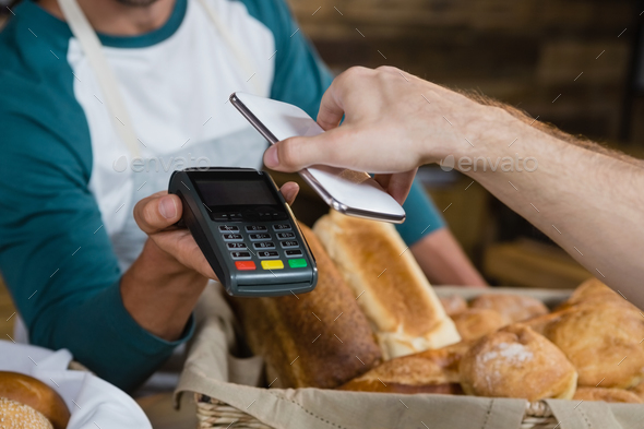 Customer paying bill through smartphone using NFC technology at counter - Stock Photo - Images