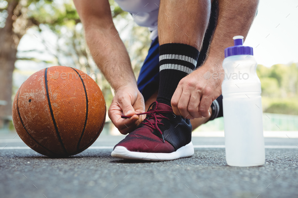 Low section of basketball player tying shoelace - Stock Photo - Images