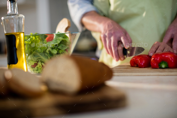 Senior man helping woman to cut vegetable in kitchen - Stock Photo - Images