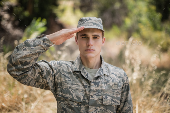 Portrait of military soldier giving salute - Stock Photo - Images