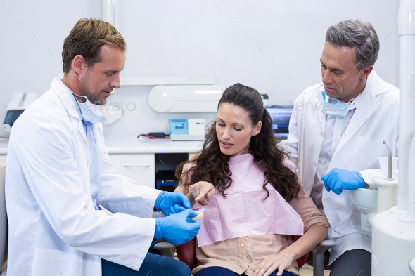 Dentist showing model teeth to patient - Stock Photo - Images