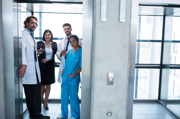 Doctors and businesswoman standing in elevator - Stock Photo - Images