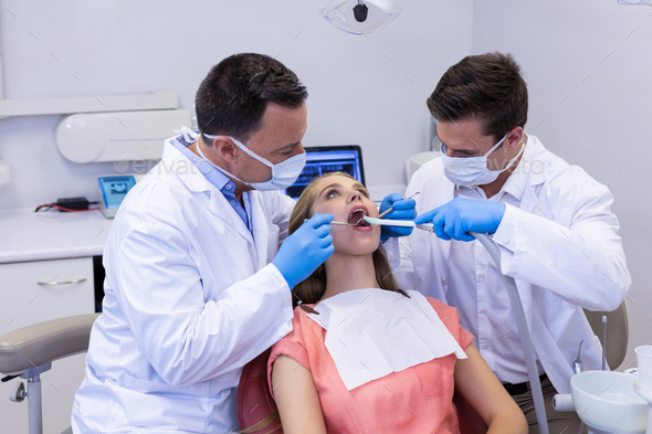 Dentists examining a male patient with tools - Stock Photo - Images