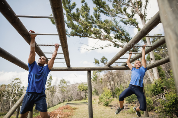 Fit man and woman climbing monkey bars during obstacle course - Stock Photo - Images